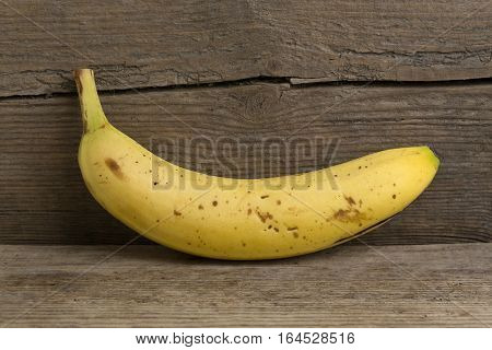 Crooked yellow banana on a wooden background