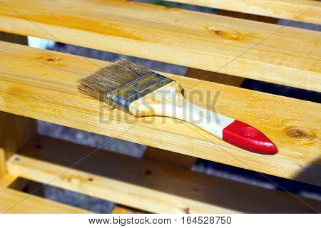 Brush lying on a painted wooden shelving surface. Photo closeup