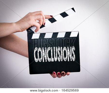 Conclusions. Female hands holding movie clapper. Gray background.