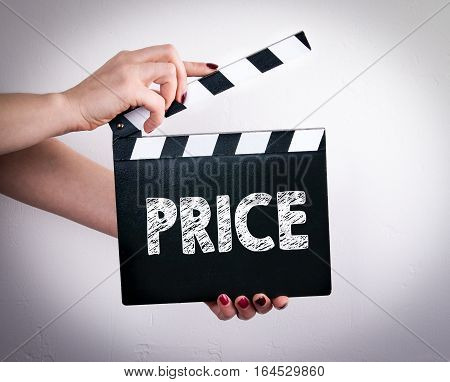 Price. Female hands holding movie clapper. Gray background.