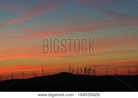 red sunset and wind turbine in a eolic park