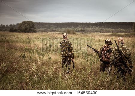 Hunters in camouflage walking through rural field during hunting season season in overcast day with moody sky