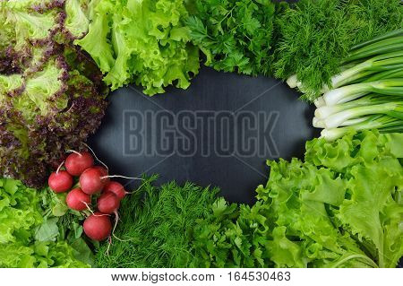 Fresh vegetables and spices on a dark wooden background. Top view. Concept. Proper nutrition. Organic products. Spring. Vitamins. Diet. Vegetarianism.
