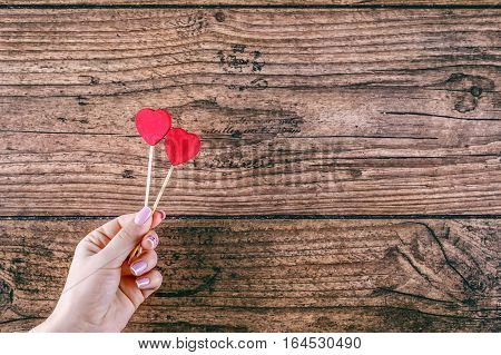 Woman's hand holding two red hearts shape on stick. Dark wooden baskground. Valentine concept
