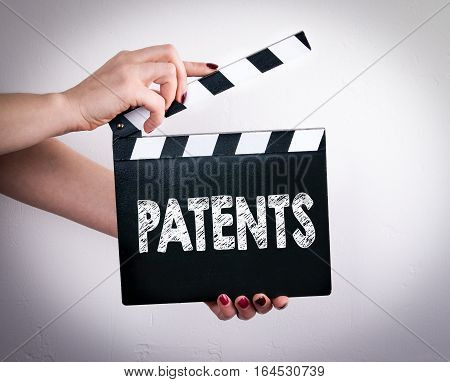 Patents. Female hands holding movie clapper. Gray background.