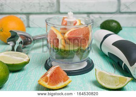 Fresh smoothie ingredients and blender. Citrus orange lime in the blender on kitchen table