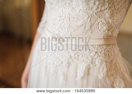 beautiful white lacy wedding dress of the bride close up. Detail of wedding dress - beautiful lace.