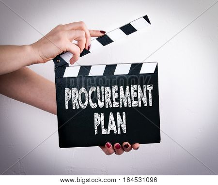 Procurement Plan. Female hands holding movie clapper. Gray background.