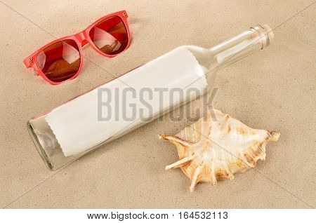 Message in a glass bottle lies on the sand beach with seashells and sunglasses