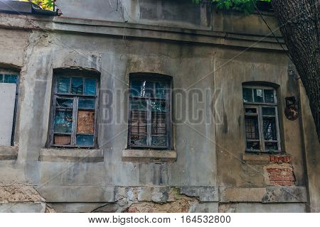 Broken and boarded-up windows of the old abandoned house, Voronezh, Russia