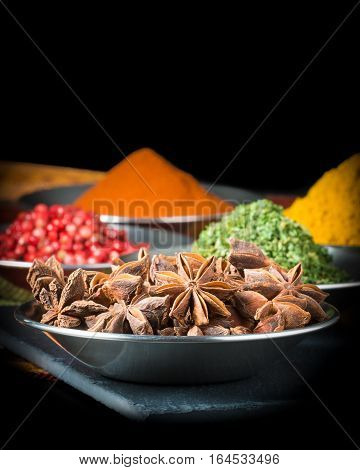 Closeup photograph of star of anise with other clorful spices in the background.