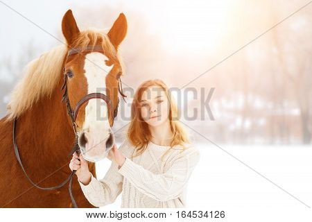 Young teenage happy girl with bay horse in winter park