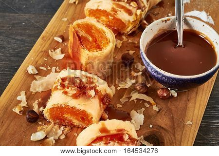 Pumpkin strudel with chocolate sauce on cutting board