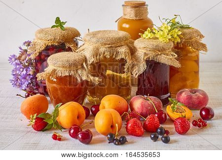 Various jams and compotes with fresh fruits on white wood