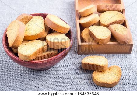 Pieces Of Rusk In The Old Brown Wooden Bowl On A Gray Tablecloth