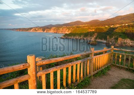 Fragment of a rural fence at sunset. On the high rocky ocean coast summer evening a fence is lit with the setting sun focus on a fence