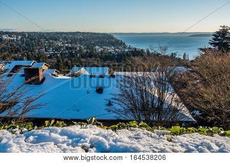 Snow cover roofs of home in Burien Washington. The Puget Sound can be seen in the distance.