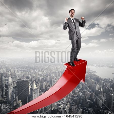 Businessman exults over a red uphill arrow. Economic success concept