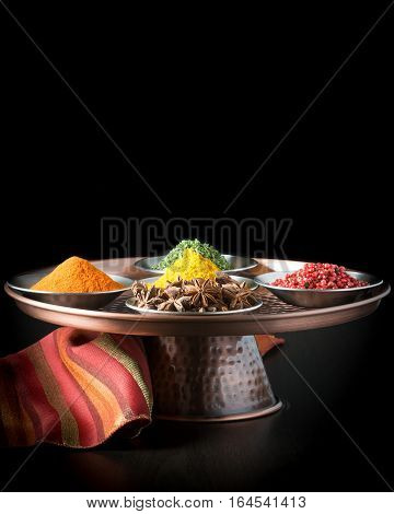 Colorful array of five spices on a copper presentation platter.