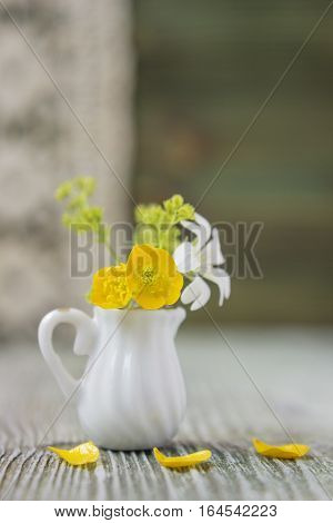 Ranunculus bouquet in miniature diminutive jug. Macro close-up photo with soft focus bouquet of buttercup flowers. Rustic colored wooden background