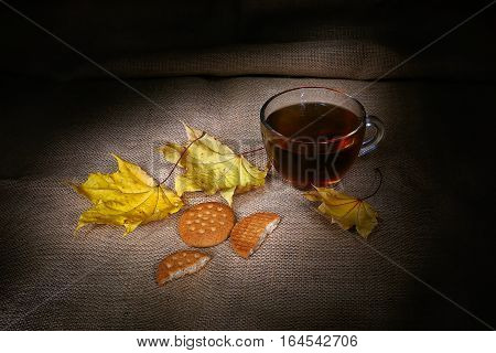 autumn leafage with warm tea in glass cup