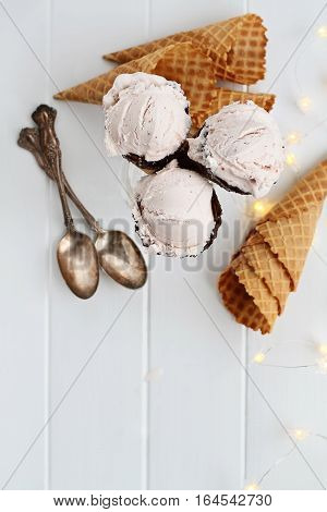 Top view of pink strawberry ice cream in waffle cones shot over a rustic wooden background with fairy lights and antique spoons. Extreme shallow depth of field.