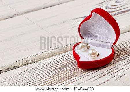 Pearl earrings in heart-shaped box. Red case on wooden background. Romantic and valuable gift.