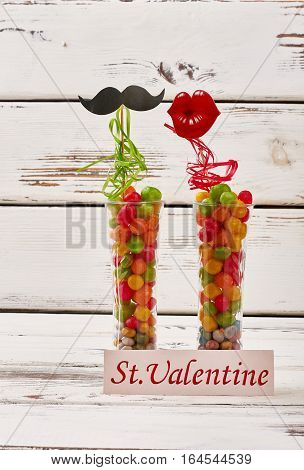 Props on Valentine's Day. Card near vases with candies. Theme of party.