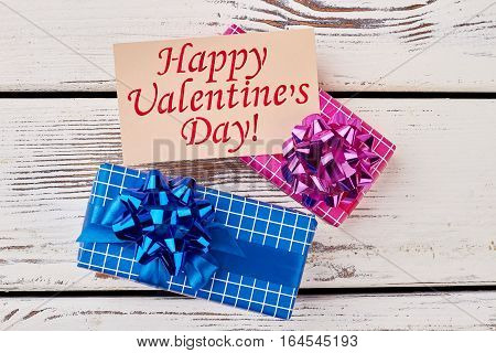Presents and Valentine's Day card. Gift boxes on wooden backdrop. Pleasant moments with beloved.
