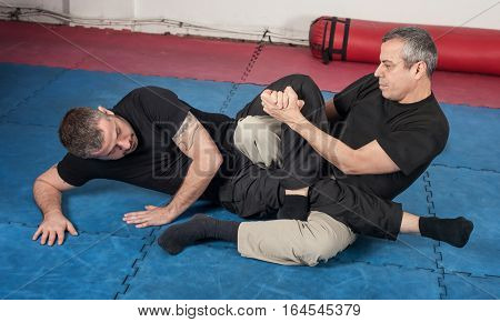 Kapap instructor demonstrates ground fighting techniques with his student