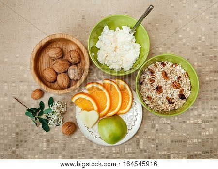 Top View.Table Appointments for Healthy Organic Breakfast.Walnuts,Oatmeal and Cottage Cheese.Cut Orange and Apple.Green Ceramic and Wooden Plates with Flowers.