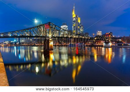 Picturesque view of Frankfurt am Main skyline and Eiserner Steg bridge with mirror reflections in the river during morning blue hour, Germany