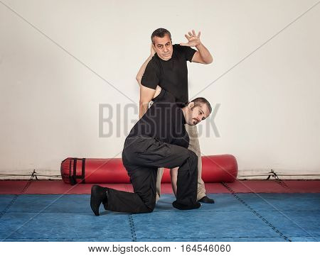 Kapap instructor demonstrates standing arm lock techniques with his student