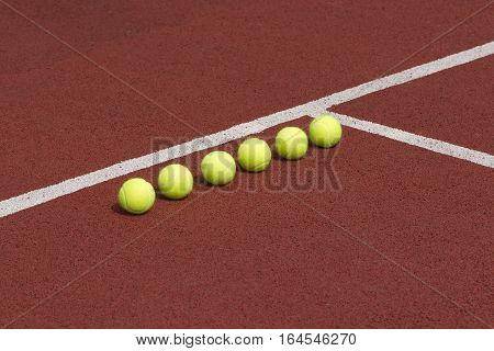 Line of six yellow tennis balls on court side view