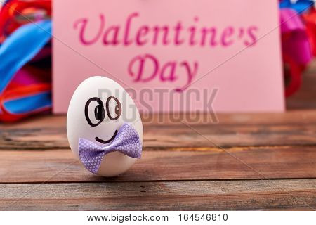 Valentine's Day card near egg. Egg with face and bow. Cute surprise for beloved.