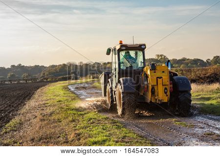 Large yellow tractor on a wet country path. Taken on a walk over farmland near the village of Abridge in Essex England in autumn.