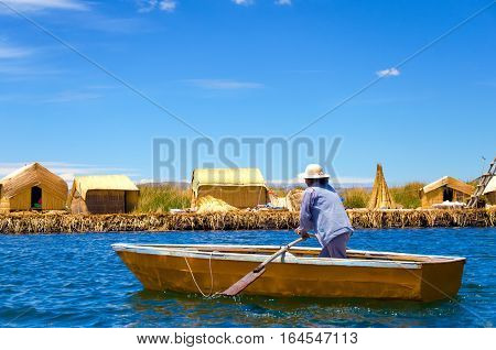 UROS FLOATING ISLANDS PERU - SEPTEMBER 19: Woman in a small boat in the Uros Floating Islands Peru on September 19 2014
