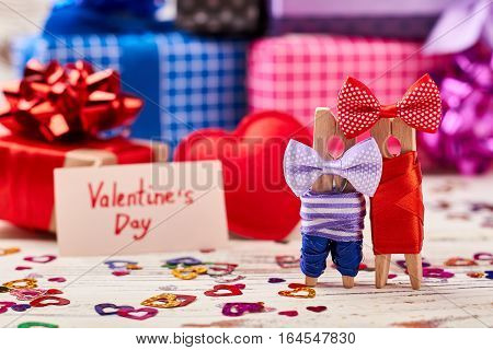 Clothespin couple on Valentine's Day. Hearts, gift boxes, greeting card. Forever in love.