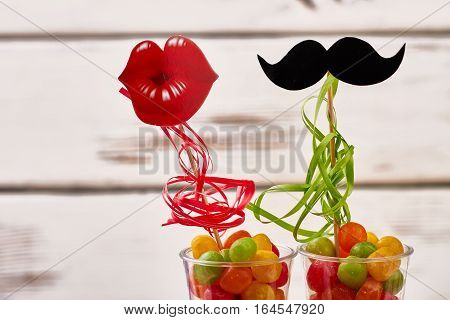 Props lips, mustache with candies. Colorful sweets in glass. Creativity has no borders.