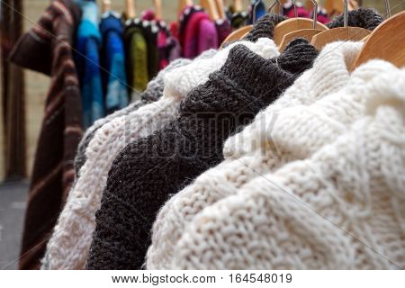 Black And White Thick Knitted Wool Winter Jumpers And Jackets For Sale On A Marlet Stall
