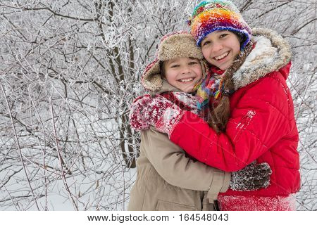 Two kids standing together on winter forest, outdoors vacation, empty space for text