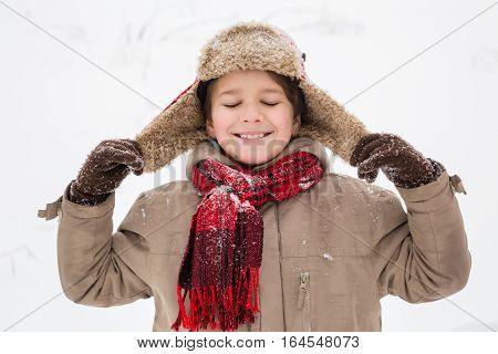 Adorable boy enjoying the winter, outdoors snow landscape