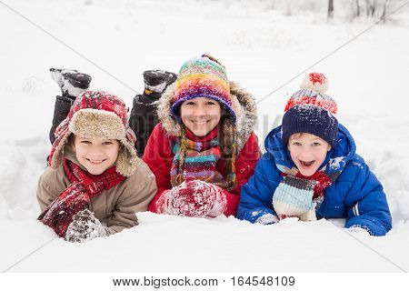 Three kids lying down together on white snow, outdoors winter vacation