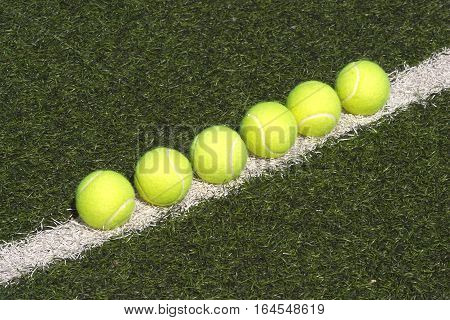 Yellow tennis balls lays in-line on court with green synthetic grass side view