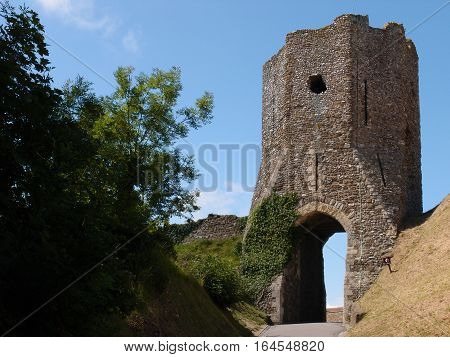 A stone lookout tower at Dover Castle in England with a walk through arch on the side of a hill with ivy climbing up the front on a summer day.