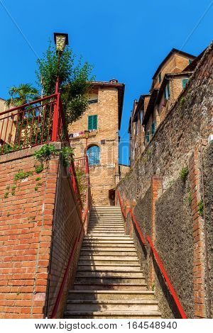 steep alley in the old town of Siena Tuscany Italy