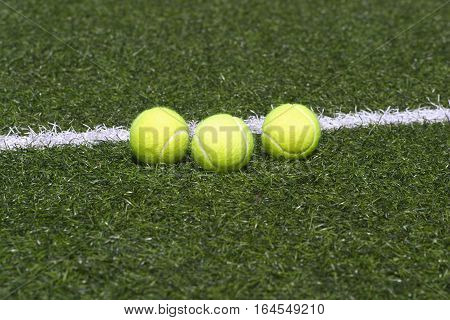 Three yellow tennis balls lays on grass court line front view