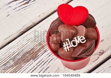Love hashtag and red heart. Chocolate candies in flower pot. Make every day like holiday.