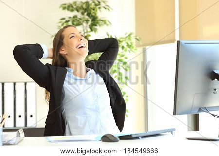 Satisfied businesswoman with arms on the head laughing sitting on a chair and relaxing at office