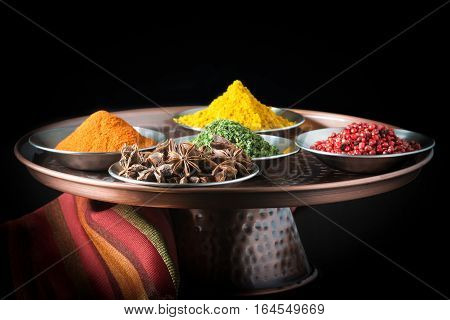 Five colorful spices on a copper presentation plate.